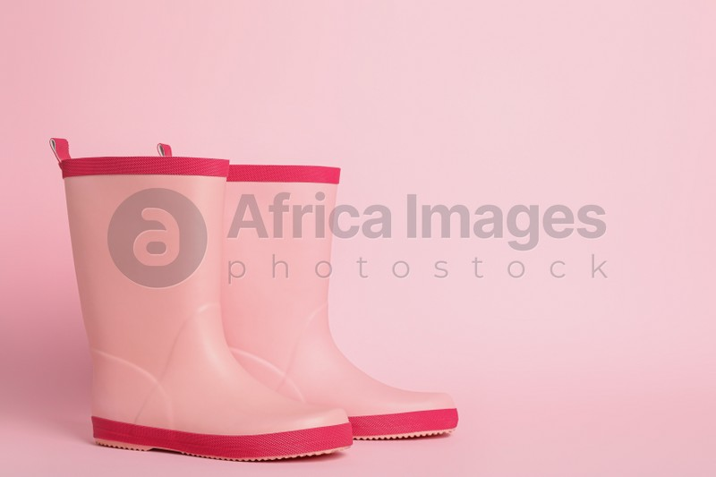 Pair of rubber boots on pink background. Space for text