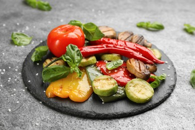 Delicious grilled vegetables with basil on grey table