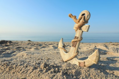 Wooden anchor with rope on sand near sea. Space for text