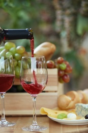 Pouring red wine from bottle into glass on table in vineyard