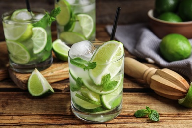 Delicious mojito and ingredients on wooden table
