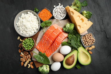 Products rich in protein on black table, flat lay