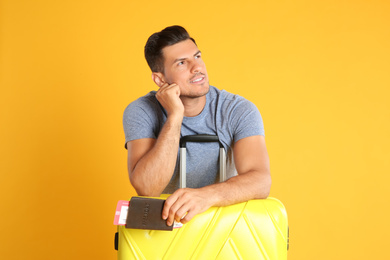 Handsome man with suitcase and ticket in passport for summer trip on yellow background. Vacation travel
