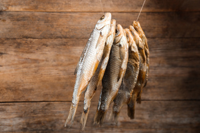 Dried fish hanging on rope against wooden background