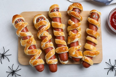 Cute sausage mummies served on white table, flat lay. Halloween party food