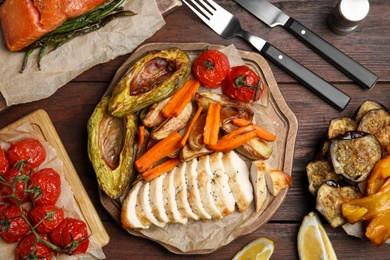 Tasty cooked chicken fillet and vegetables served on wooden table, flat lay. Healthy meals from air fryer