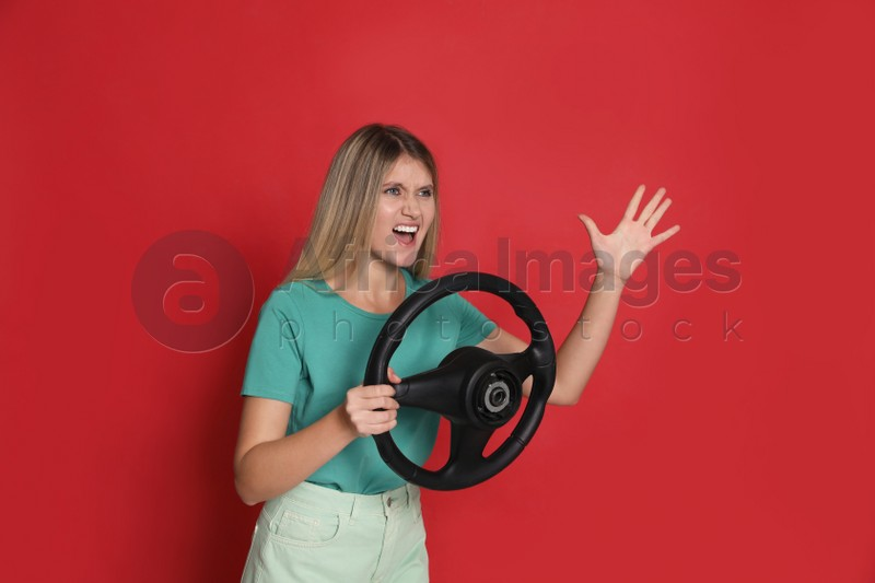 Emotional young woman with steering wheel on red background