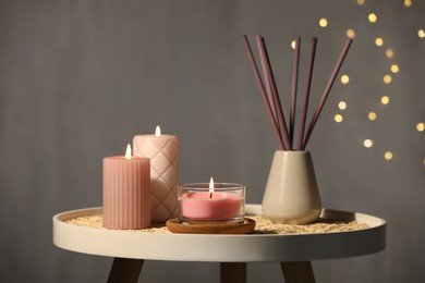 Burning candles and reed diffuser on table against grey background