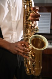 African-American man playing saxophone indoors, closeup. Talented musician
