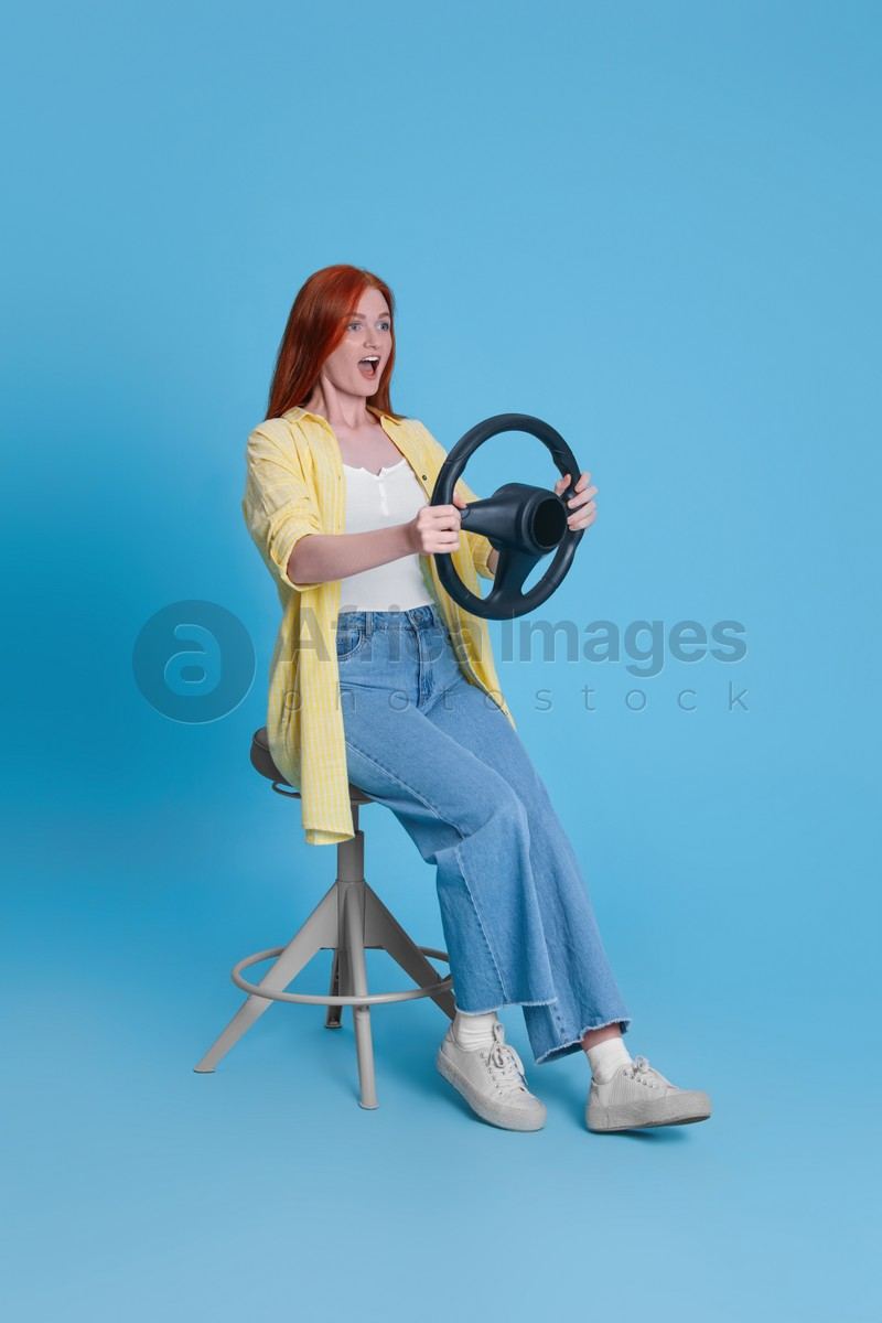 Emotional young woman on chair with steering wheel against light blue background
