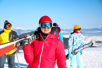 Young woman with ski at resort. Winter vacation