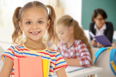 Happy girl with notebooks in school classroom