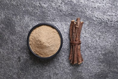 Powder in bowl and dried sticks of liquorice root on grey table, flat lay