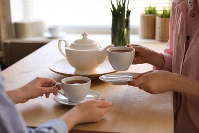 Women with cups of tea at table near window indoors, closeup