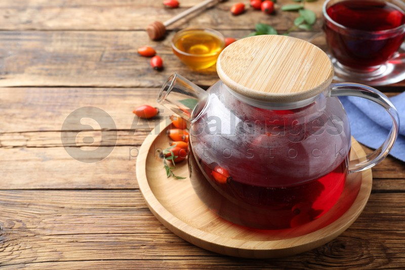 Teapot with aromatic rose hip tea and fresh berries on wooden table, space for text