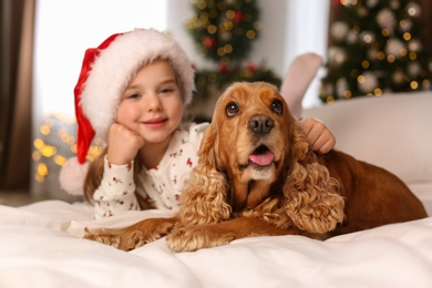 Cute little girl with English Cocker Spaniel on bed in room decorated for Christmas