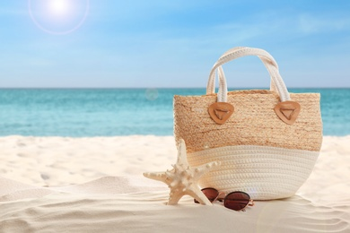 Bag and stylish glasses on sand near ocean, space for text. Beach accessories