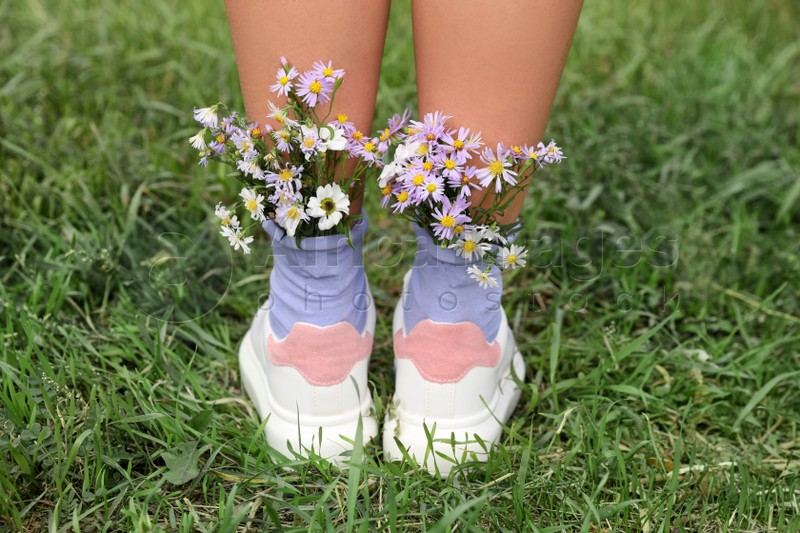 Woman with beautiful tender flowers in socks on green grass, closeup
