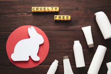 Cubes with text Cruelty Free, personal care products and figure of rabbit on wooden table, flat lay. Stop animal tests