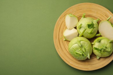 Whole and cut kohlrabi plants on green background, top view. Space for text