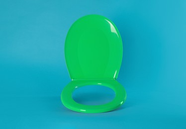 New green plastic toilet seat on light blue background, space for text