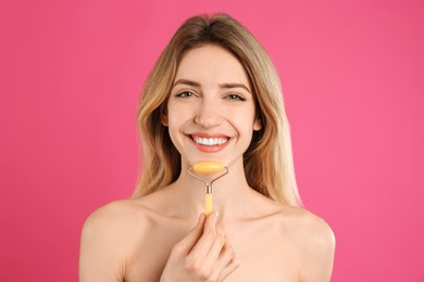 Young woman using natural jade face roller on pink background