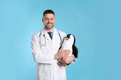 Pediatrician with toy penguin and stethoscope on light blue background