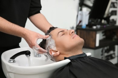 Professional barber washing client's hair at sink in salon, closeup