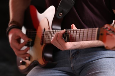 Man playing electric guitar on stage, closeup. Rock concert