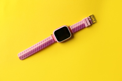 Trendy smart watch for kids on yellow background, top view