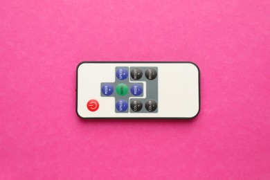 Remote control on pink background, top view