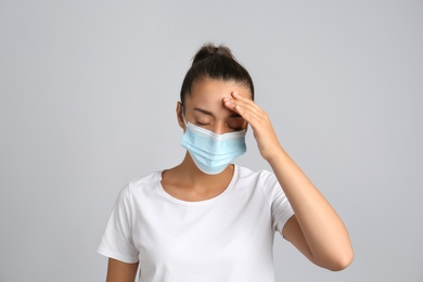 Stressed woman in protective mask on grey background. Mental health problems during COVID-19 pandemic