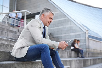 Portrait of handsome businessman with mobile phone in city