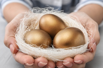 Woman holding nest with golden eggs over table, closeup