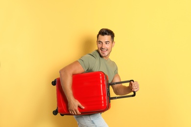 Young man running with suitcase on color background