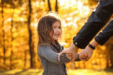Cute little girl with mother in sunny park. Autumn walk