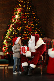 Santa Claus giving present to little boy near Christmas tree indoors