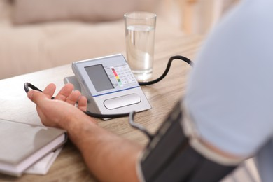 Man checking blood pressure at wooden table indoors, closeup