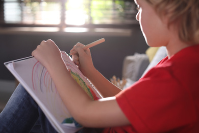 Little boy drawing at home, closeup. Creative hobby