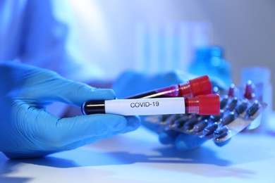 Scientist holding pills and test tubes of blood samples with label Covid-19 at table, closeup