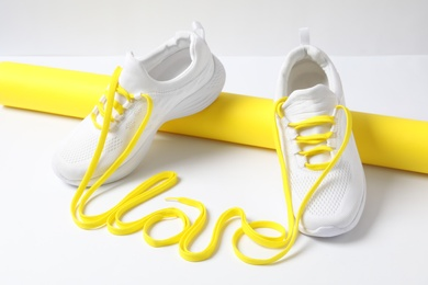 Stylish sneakers and word Love made with yellow shoe laces on white background