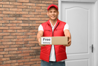 Courier holding parcel with sticker Free Delivery indoors