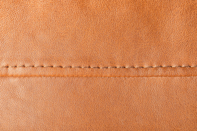 Texture of orange leather as background, closeup