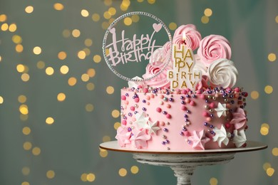 Beautiful birthday cake with decor on stand against festive lights. Space for text