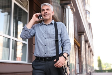 Handsome businessman talking by mobile phone in city, space for text