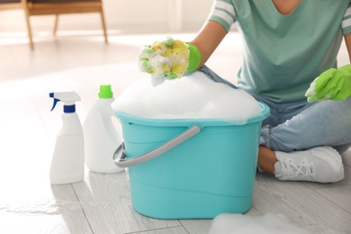 Woman holding sponge with foam over bucket indoors, closeup. Cleaning supplies