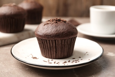 Delicious cupcake with chocolate crumbles on beige marble table, closeup
