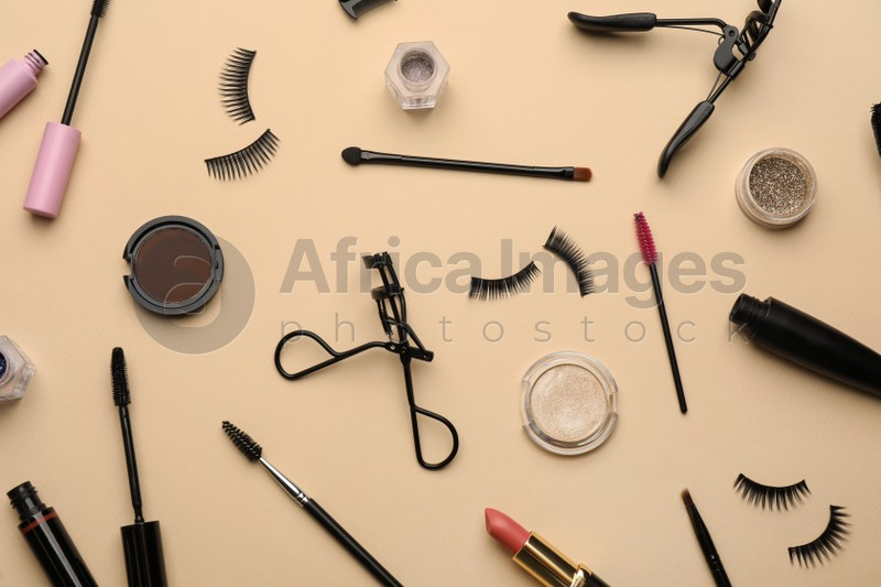 Flat lay composition with eyelash curlers, makeup products and accessories on beige background