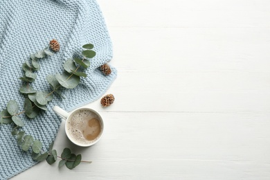 Flat lay composition with coffee and warm plaid on white wooden table, space for text
