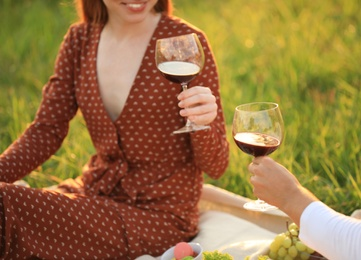Young couple with wine having picnic in green park, closeup